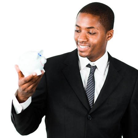 Close-up of an young African businessman looking at a piggy bank photo