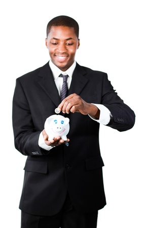 Smiling Afro-American businessman putting money in his piggy bank photo