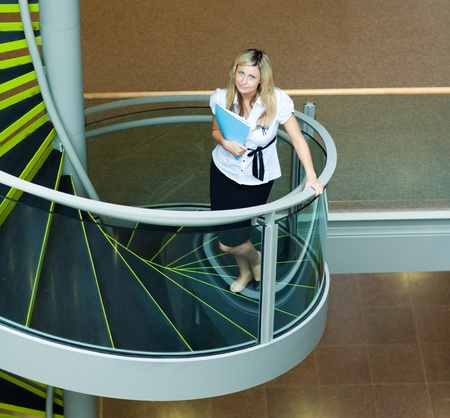going up: Businesswoman walking up stairs in office Stock Photo