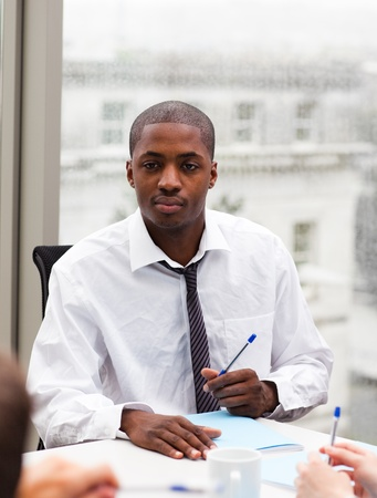 Afro-American businessman writing in an office photo