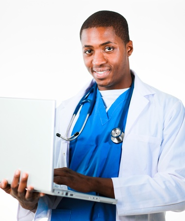 Handsome doctor working on a laptop and smiling at the camera photo
