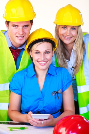 Team of three with hard hats at work smiling at the camera photo