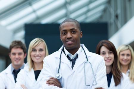 estudiantes medicina: Doctor afroamericana liderando a su equipo con los brazos doblados Foto de archivo