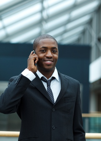 Ethnic businessman on phone and smiling at the camera photo