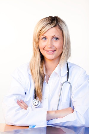 Blonde doctor sitting in an office and smiling at the camera photo