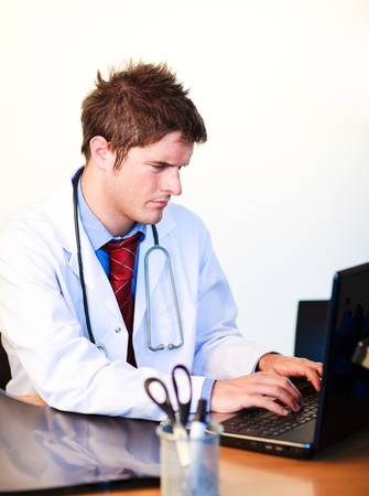 Thoughtful  young doctor working on a computer photo