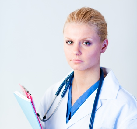 Serious doctor holding a clipboard photo