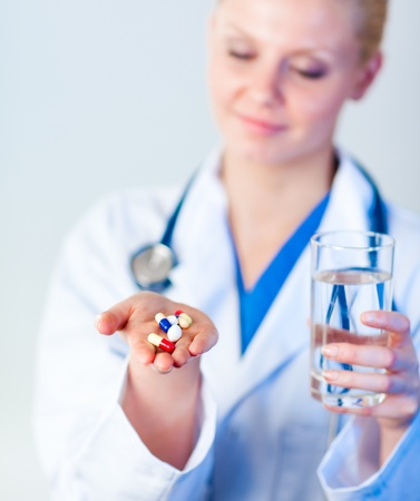 Doctor holding pills to camera photo