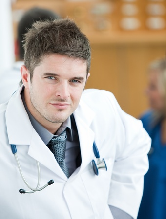 Portrait of a handsome surgeon with his team behind him photo