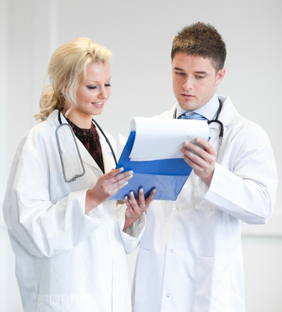 Two nice doctors looking at a report photo