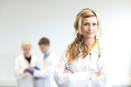Beautiful female surgeon with her team behind her photo