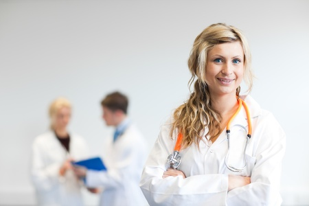 Pretty female surgeon with her team behind her photo