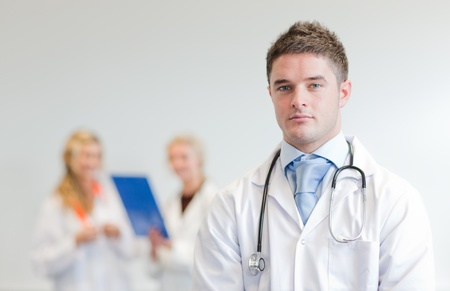 Self-assured male surgeon with his team behind him photo