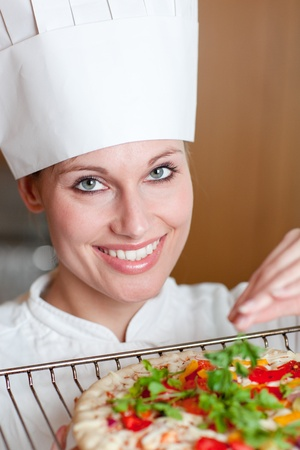 Radiant female chef cooking a pizza Stock Photo - 10112669