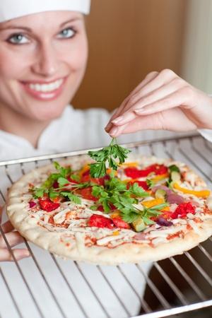 Lumineux chef féminin de cuisson d'une pizza