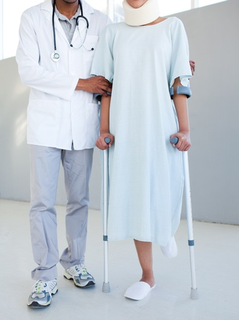 A physical therapist helping a patient with neck brace and on crutches photo