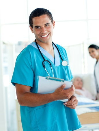 Attractive male doctor holding a medical clipboard photo