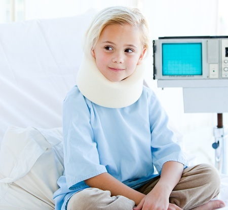 Little girl with a neck brace sitting on a hospital bed  photo