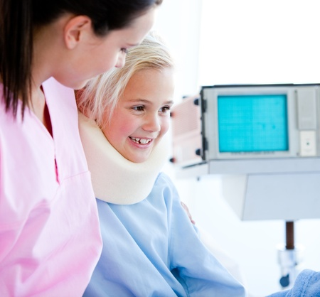 Smiling little girl with a neck brace sitting on a hospital bed  photo