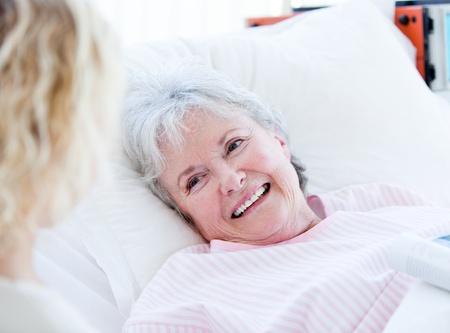 test probe: Sorridente donna anziano sdraiato su un letto d'ospedale a parlare con sua nipote
