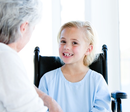 Blond little girl sitting on a wheelchair talking with her grandmother  photo
