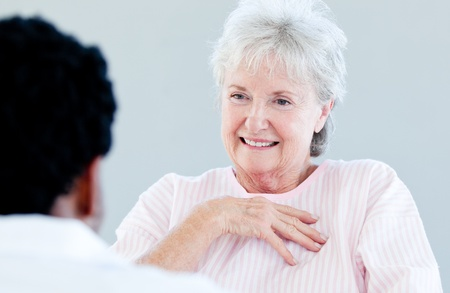 Smiling senior patient sitting on a wheelchair talking with her doctor photo