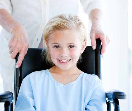 little girl smiling: Adorable little girl sitting on a wheelchair