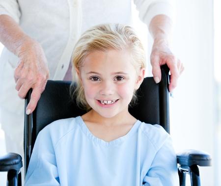 hospital equipment: Adorable little girl sitting on a wheelchair