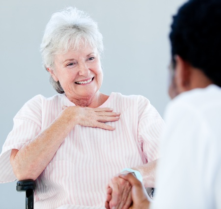 Senior woman sitting on a wheelchair talking with her doctor photo