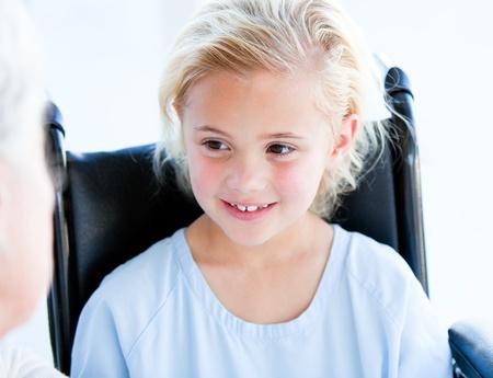test probe: Blond bambina seduta su una sedia a rotelle Archivio Fotografico