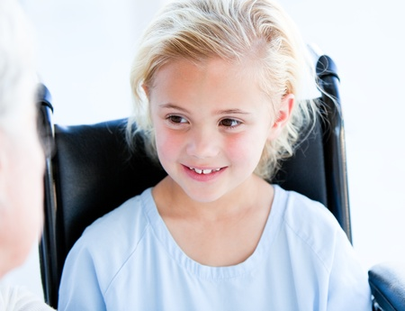 Blond little girl sitting on a wheelchair photo