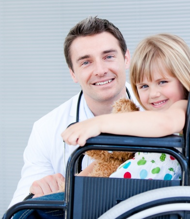 disable: Cute little girl sitting on a wheelchair with her doctor