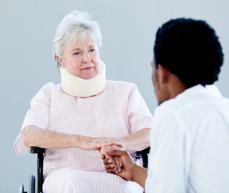 neck brace: Senior woman sitting on a wheelchair with a neck brace talking with her doctor
