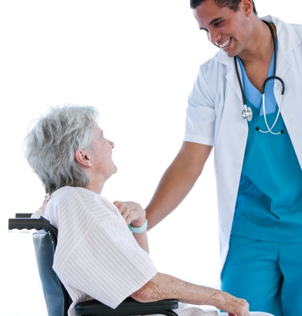 Senior patient sitting on a wheelchair talking with her doctor against a white background photo