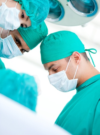 teaming: Multi-ethnic madical team working on a patient  Stock Photo