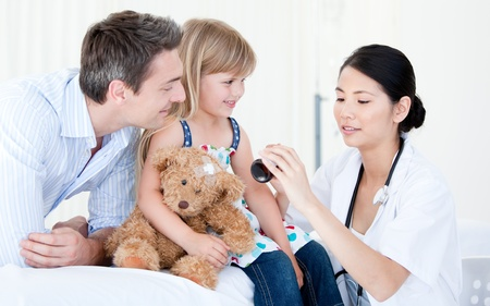 Concentrated asian female doctor giving syrup to a little girl Stock Photo - 10111053