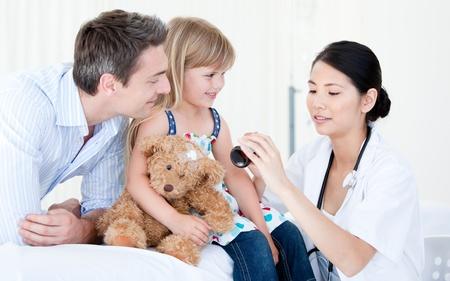 Konzentrierte asiatischen weiblichen Arzt, der Sirup zu einem kleinen M�dchen