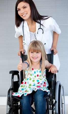 handicapped accessible: Smiling little girl sitting on the wheelchair