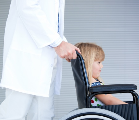 supported: Smiling little girl sitting on the wheelchair supported by a doctor