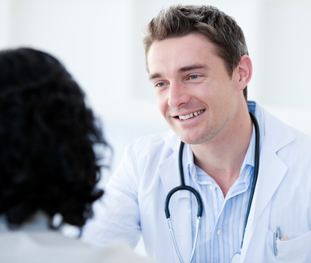 Portrait of a handsome doctor talking with his patient for the annual check-up  photo