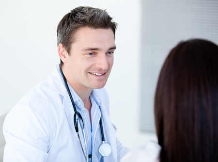 Smiling doctor talking with his patient  photo