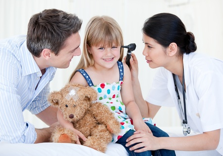 asian doctor: Smiling girl looks happy with her teddy bear  Stock Photo