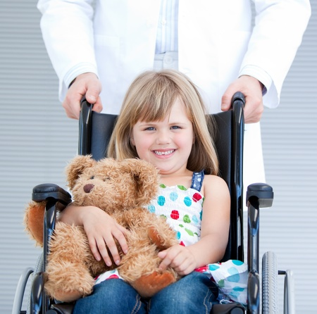 Portrait of a little girl sitting on the wheelchair supported by a male doctor photo