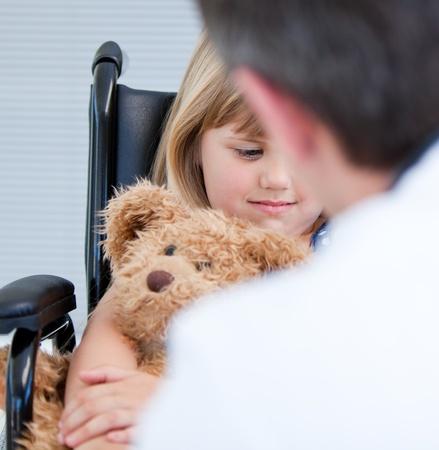 niños discapacitados: Médico hombre hablando con una niña con discapacidad