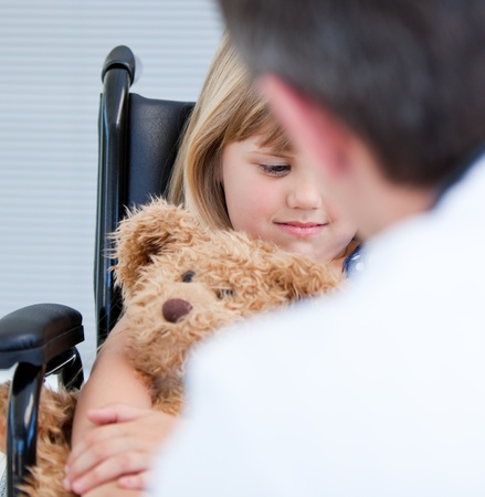 Male doctor talking with a disabled little girl photo