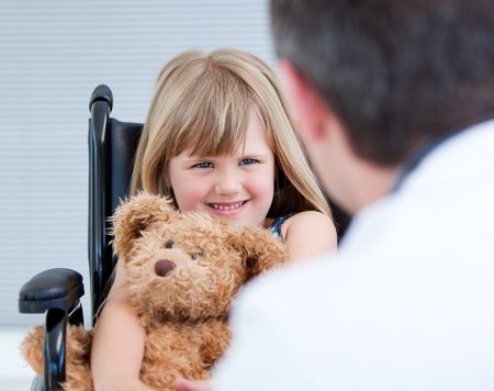 Smiling little girl sitting on the wheelchair with her teddy bear photo