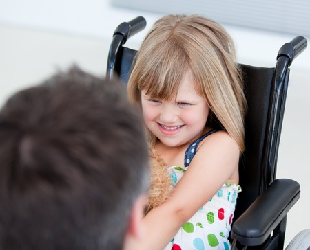 wheelchair man: Reserved little girl sitting on the wheelchair Stock Photo