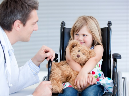 disable: Smiling little girl sitting on the wheelchair lokking at the doctor