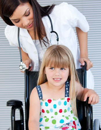 Smiling cute girl sitting on the wheelchair photo