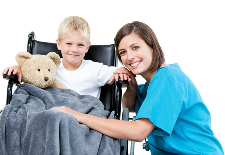 Nice female doctor carrying adorable little boy with his teddy bear in the wheelchair at the hospita photo